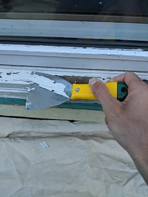 scraping old paint with putty knife