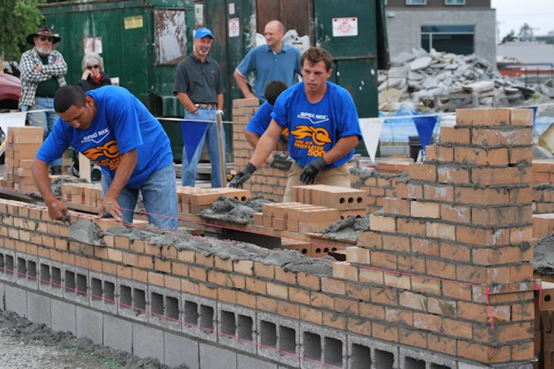 bricklayers installing brick wall with mortar