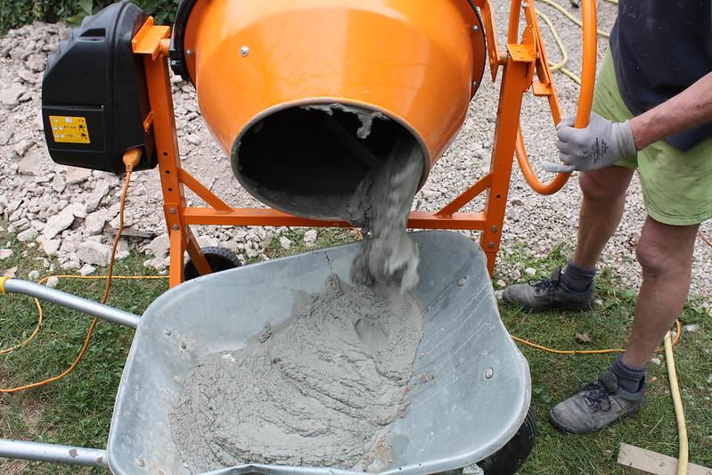 concrete mixer pouring into wheelbarrow