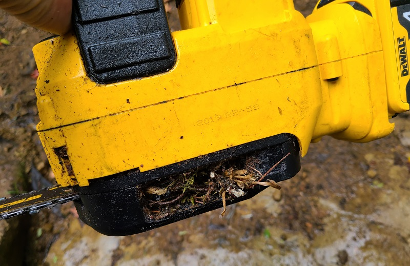 chainsaw with debris buildup inside cover plate
