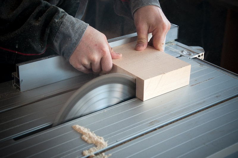 person cutting wood on table saw