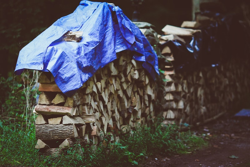 cords of wood covered with tarp for winter